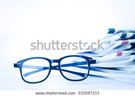 selective focus on reading eyeglasses with stacking of the newspaper background ,business information concept - stock photo