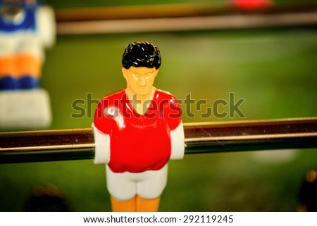 Selective focus on Single Player in Red Jersey, Vintage Foosball, Table Soccer or Football Kicker Game, Retro Tone Effect - stock photo