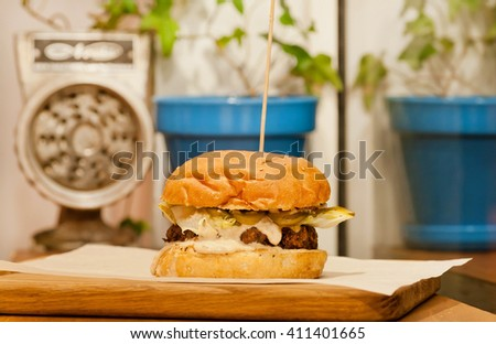 Selective focus on small burger with fresh vegetables, meat and bun. Best fast-food choice with vintage grinder. - stock photo