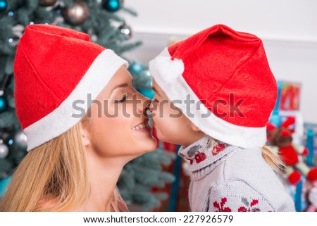 Selective focus on smiling beautiful mom and daughter wearing red caps of Santa Claus sitting opposite each other touching with their noses - stock photo