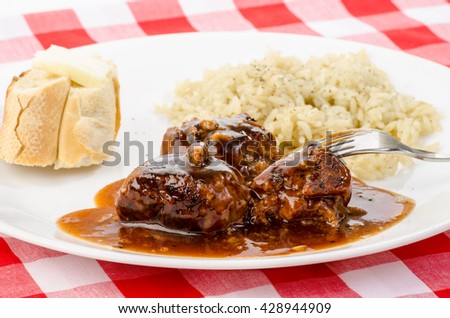 Selective focus on Swedish Meatballs in brown gravy with buttered roll and steamed rice.