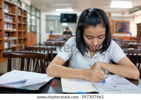 selective focus on thai young adult woman student in uniform reading a book in library with stress - stock photo
