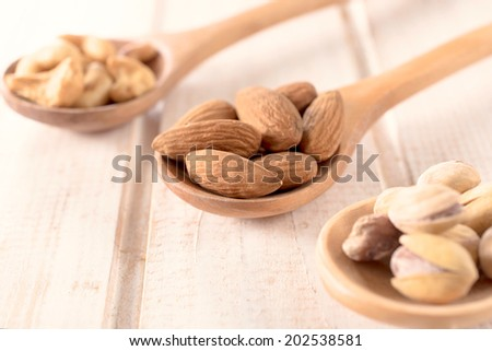 Selective focus on the almonds in wooden ladle  - stock photo