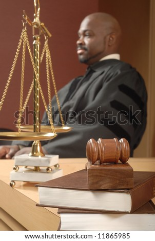 Selective focus on the books and legal research with a robed judge in the background - stock photo