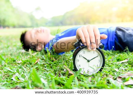 Selective focus on the classical black alarm clock model, in front of the sleeping young boy that try to stop the ring by his hand on green lawn, in the park in day time. - stock photo