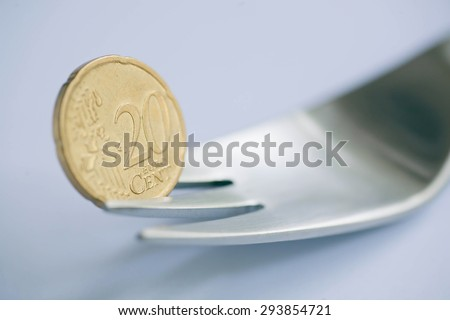 Selective focus on the coins in the twenty euro cents, a metal fork, as a symbol of the crisis - stock photo