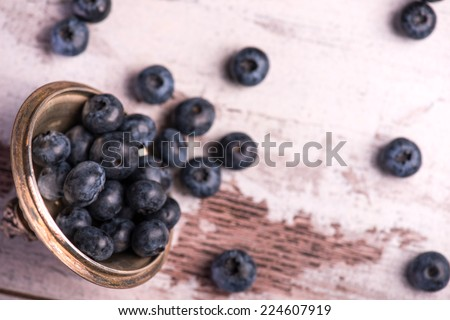 Selective focus on the copper top with little blackberries in it lying on the wooden table. Top view - stock photo