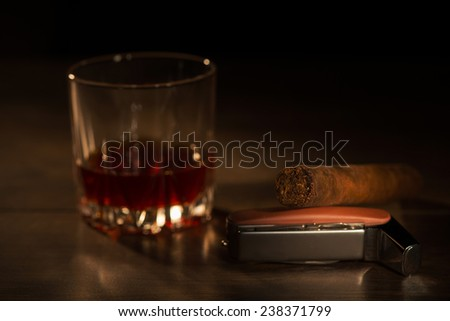 Selective focus on the Cuban cigar lying on the lighter near the glass of whiskey standing on the wooden table on background - stock photo