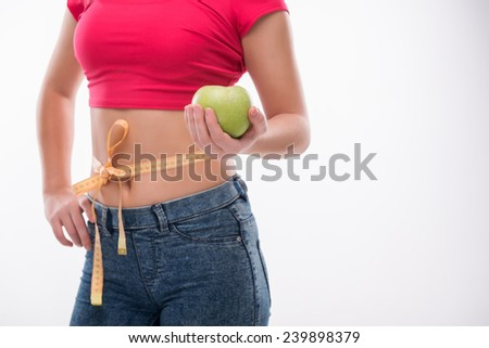 Selective focus on the delicious green apple lying in the hand of beautiful young woman wearing pink T-shirt and jeans standing with the tied tape measure on her waist on background - stock photo
