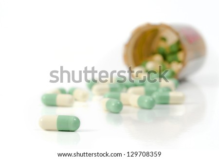 Selective focus on the foreground capsules spilled out of the pill bottle onto the white background - stock photo