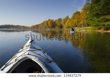 Selective focus on the foreground kayak on a tranquil autumn morning with another kayak in the distance - stock photo