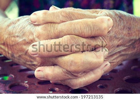 Selective focus on the front fingers on old female hands - stock photo