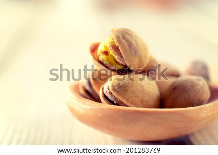 Selective focus on the front pistachios in wooden ladle - stock photo