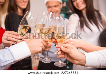 Selective focus on the glasses of champagne in the hands of friends celebrating the New Year on background - stock photo