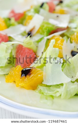 Selective focus on the grated cheese and slices of orange on a plate with salad closeup