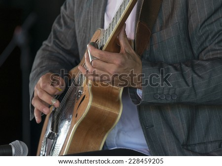 Selective focus on the hands of a guitarist playing acoustic slide  - stock photo