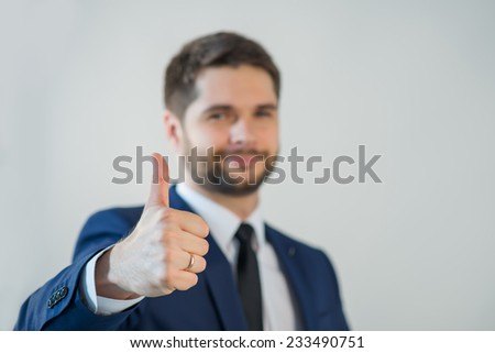 Selective focus on the hands of handsome young bearded smiling man wearing white shirt tie and blue jacket showing that everything is great - stock photo