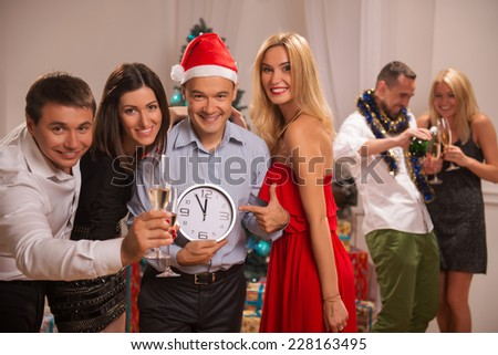 Selective focus on the happy smiling friends celebrating the New Year standing together holding a clock that shows five minute to twelve and looking at us. Two of their friends standing near the - stock photo