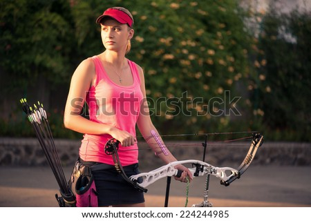 Selective focus on the lovely young fair-haired woman wearing pink T-shirt and black skirt holding the bow with arrows looking out for someone - stock photo