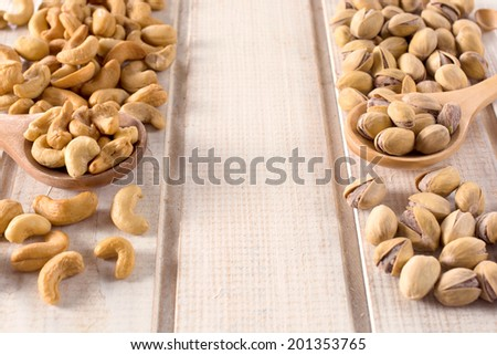 Selective focus on the nuts in wooden ladles - stock photo