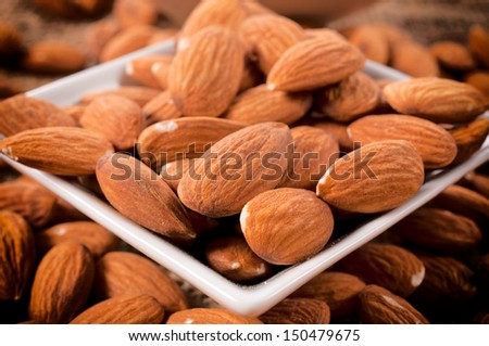 Selective focus on the raw almonds in cup - stock photo