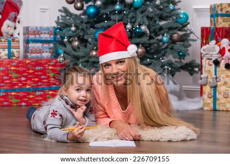 Selective focus on the smiling fair-haired mom wearing red cap lying on the floor near the Christmas tree with her little cute daughter writing a letter for Santa Claus - stock photo