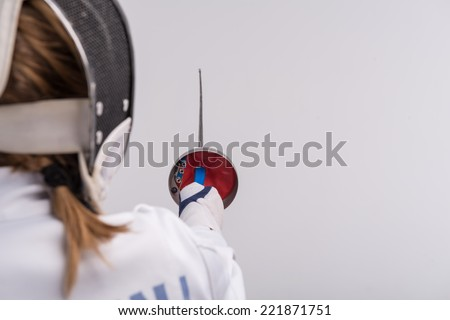 Selective focus on the sword in the hands of woman wearing white fencing costume and black fencing mask standing back to us. Isolated on white background - stock photo
