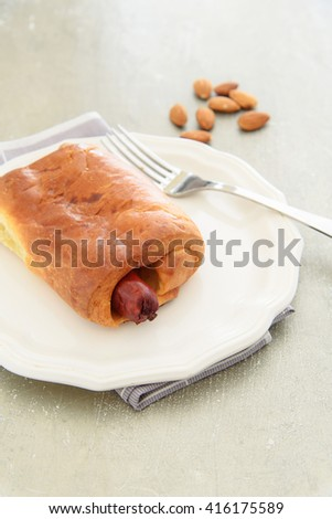 Selective focus on the tip of sausage baked in bread that look delicious on the table. - stock photo