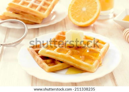 Selective focus on the waffles with butter and honey on top  - stock photo