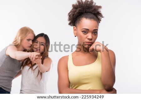 Selective focus on the young sad dark-haired girl standing alone thinking about her boyfriend. Her friends talking about her on background - stock photo
