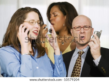 Selective focus on three businesspeople using cell phones - stock photo