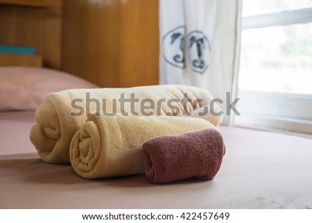 Selective focus on three different towels size on the bed next to the window in the room