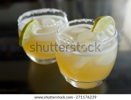 Selective focus on two margarita cocktails on the rocks with salted rim on a black glass tabletop.  - stock photo
