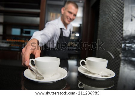 Selective focus on two white cups of coffee on the bar counter. Handsome young smiling barista wearing white shirt and black apron touching one of them on background - stock photo