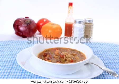 Selective focus on white bowl filled with spicy Cajun Chicken Gumbo on blue gingham place mate with ingredients in background.  Shallow Depth of Field with copy space. - stock photo