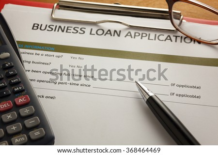 selective focus pen,Business loan application form,glasses ,calculator,red paper clip on wood background.