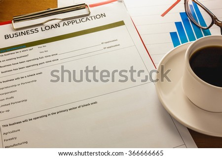 selective focus pen,Business loan application form ,summary chart black coffee,paper clip on wood background.