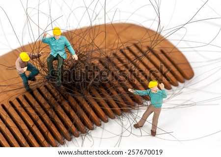 selective focus photo of miniature workers holding hair loss from wooden comb, abstract background to solution hair loss concept.  - stock photo