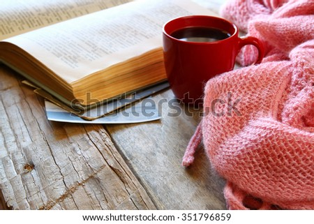 selective focus photo of pink cozy knitted scarf with to cup of coffee and open book on a wooden table  - stock photo