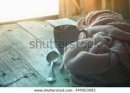 selective focus photo of pink cozy knitted scarf with to cup of coffee on a wooden table. faded style retro filtered and toned  - stock photo