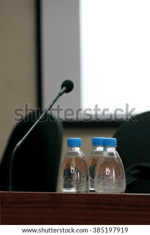 Selective focus photo of three bottles of water on table with blank screen, microphone and chairs on background in conference room - stock photo