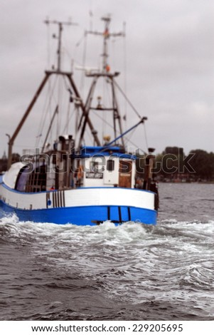 selective focus photo of waves behind an old trawler leaving the harbour of burgstaaken, fehmarn, germany - stock photo