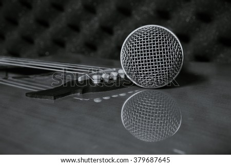 selective focus pin of classic guitar in home recording studio.Microphone on classic guitar background.