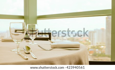 Selective focus point at Luxury banquet table near window city view , Vintage Light filter - stock photo