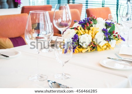 Selective focus point on wine glass with table setting for dining in restaurant