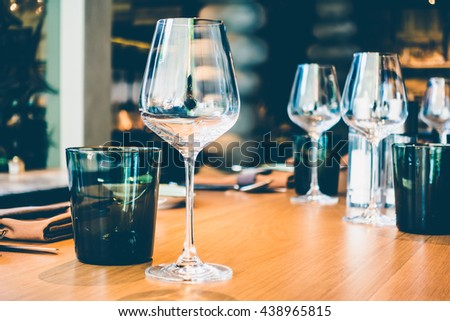 Selective focus point on wine glass with table setting for dinner in restaurant interior - Vintage Filter