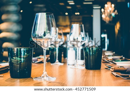Selective focus point on wine glass with table setting for dinner in restaurant interior - Vintage Filter - stock photo