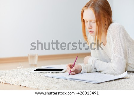 Selective focus. Portrait of pretty redhead student girl writing new words in her vocabulary while self-studying foreign languages at home. Beautiful female teenage working on her course paper - stock photo