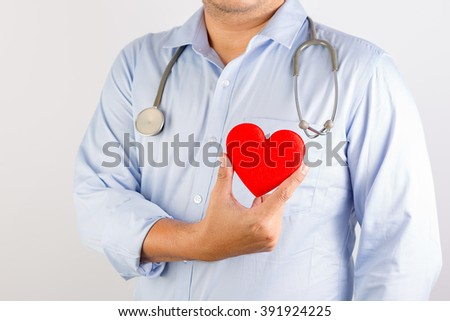 Selective Focus : Portrait of unknown male cardiologist doctor holding his stethoscope, hold red heart  , feel more confident . On gray background with shadow - stock photo