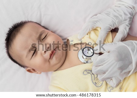 Selective focus Professional pediatrician examining infant. Doctor using a stethoscope to listen to infant's chest checking heartbeat or lung. sick baby in the hospital.